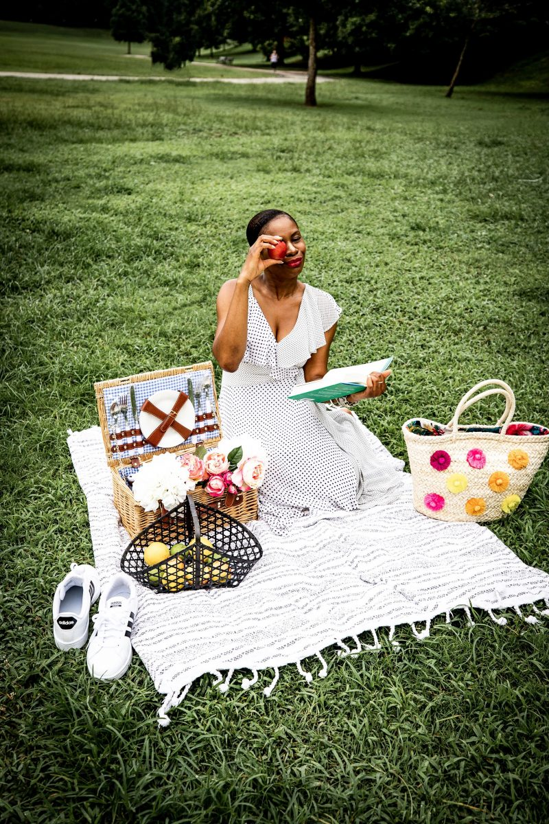 Atlanta Lifestyle Influencer Monica Awe of Awed By Monica wearing a polkadot cold shoulder dress to a picnic.