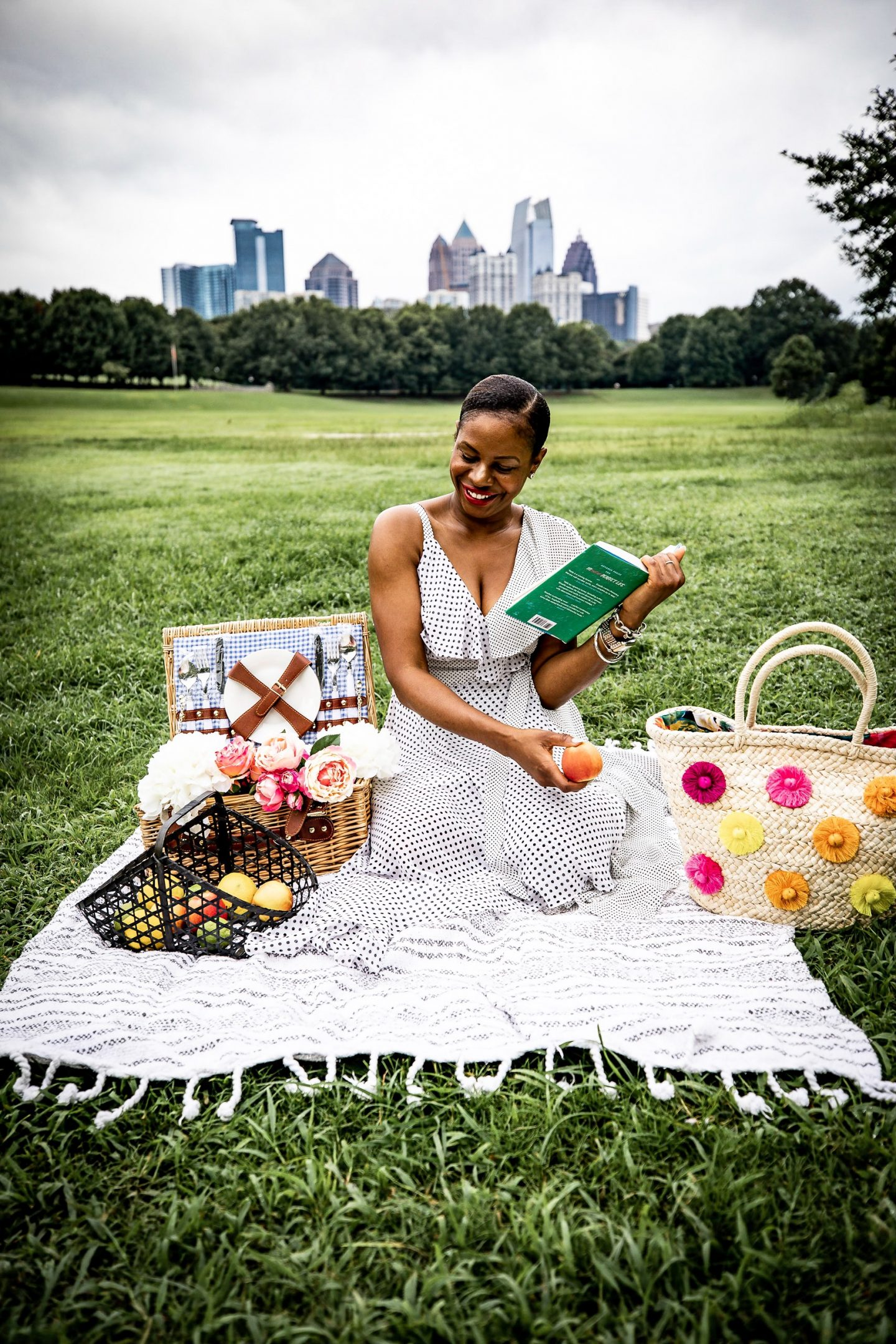 Lifestyle blogger Monica Awe of Awed By Monica wearing a polkadot cold shoulder dress from stage to a picnic.
