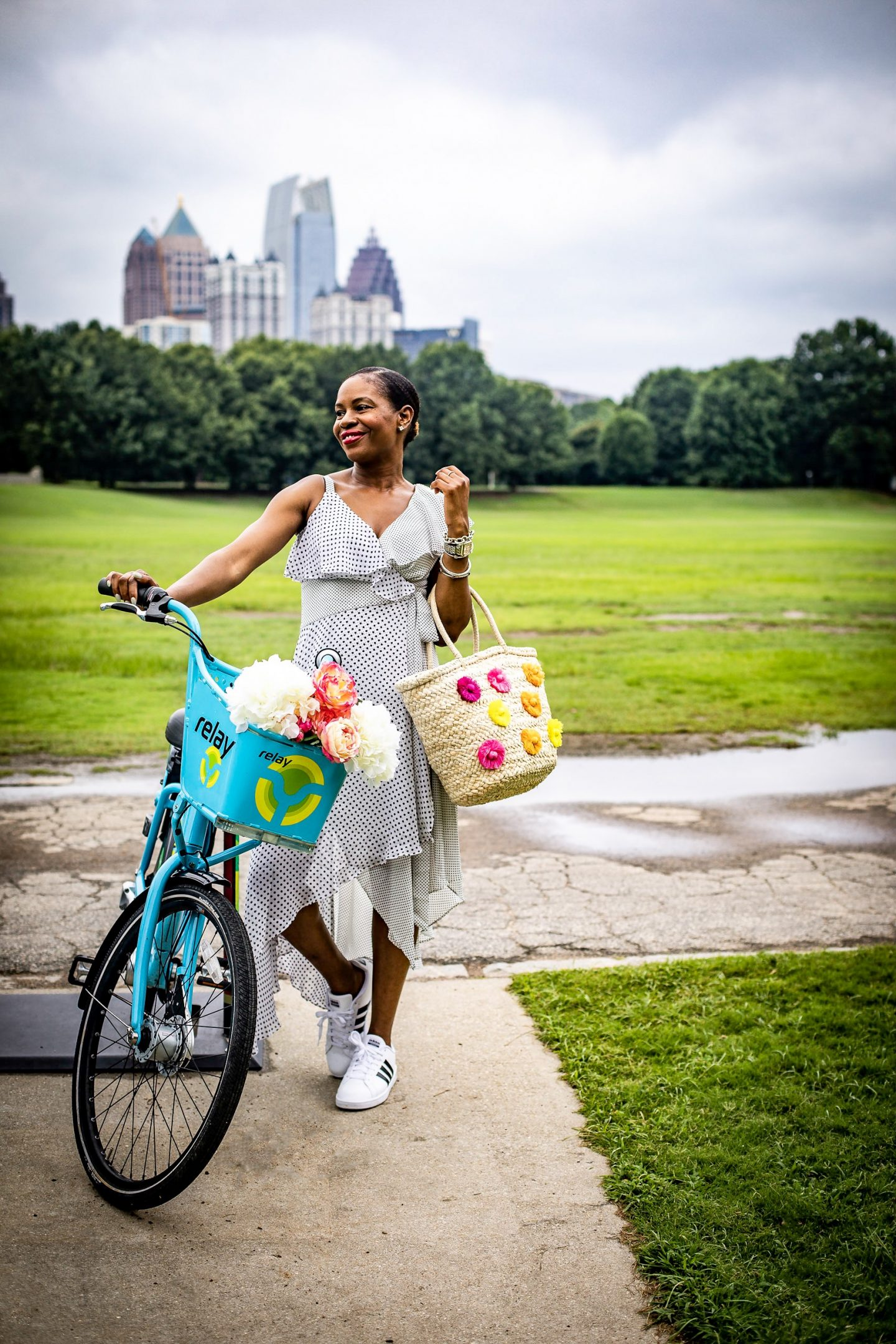 Lifestyle blogger Monica Awe of Awed By Monica wearing a polkadot cold shoulder dress for a bike ride at piedmont park