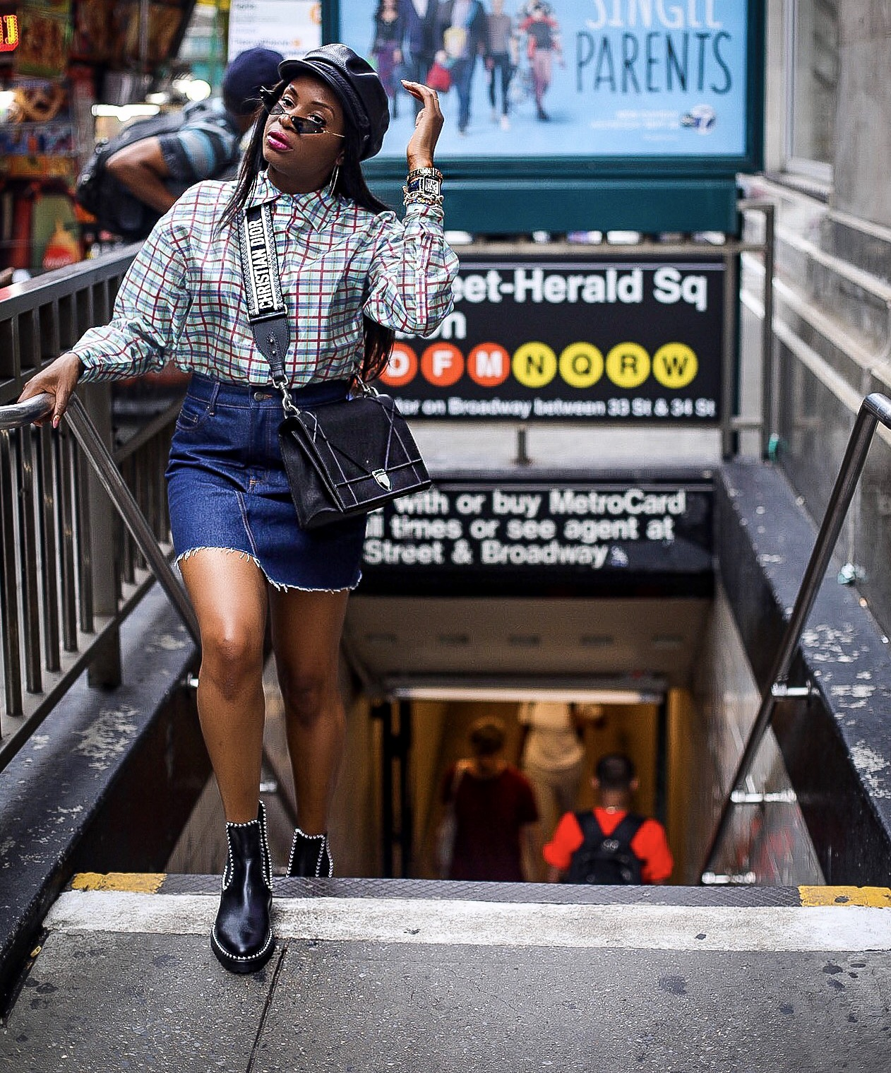 Atlanta fashion blogger Monica Awe-Etuk wearing Alexander Wang biker books, Dior saddle bag, black cap, plaid shirt and denim mini skirt.