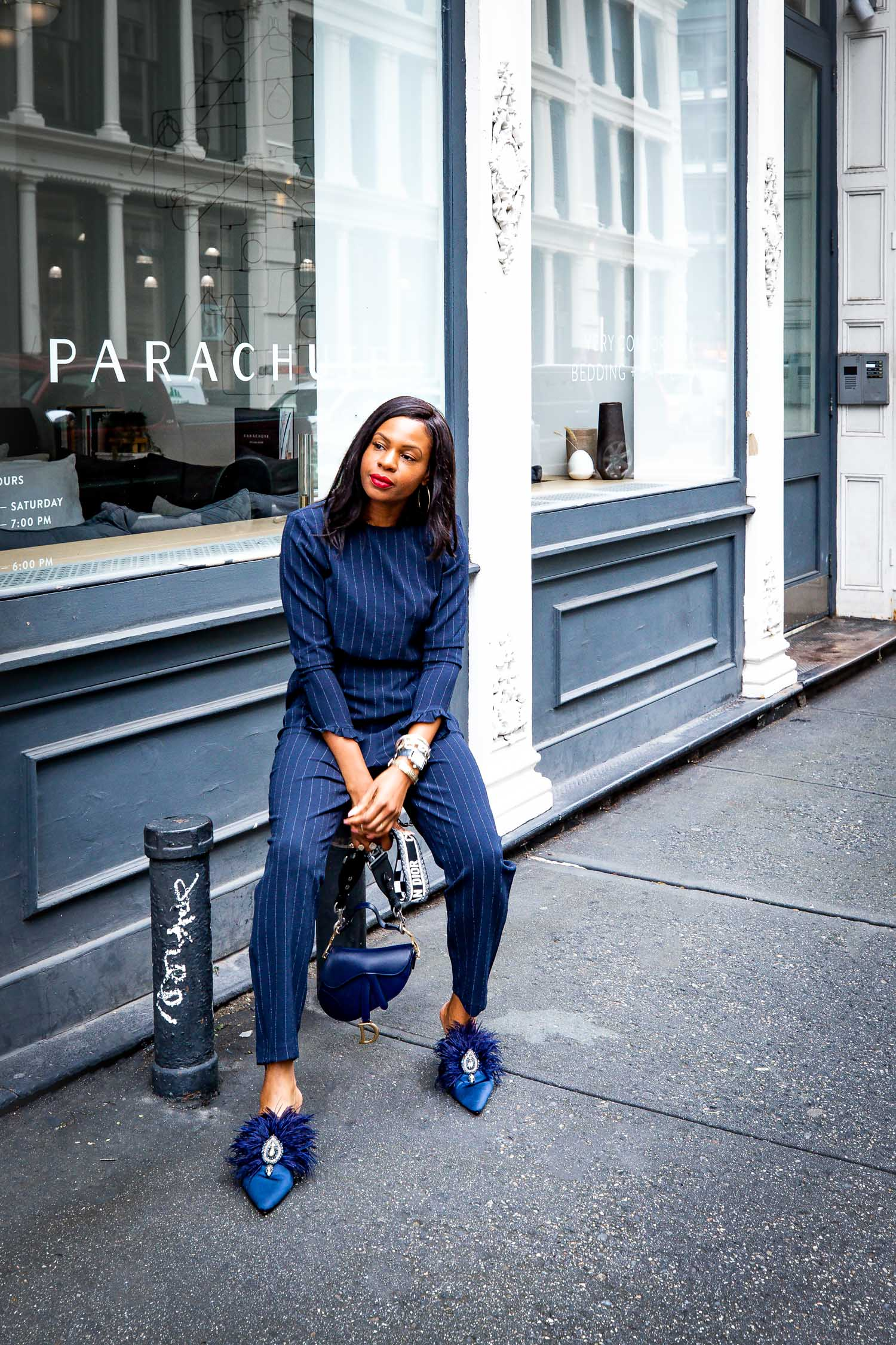 Atlanta fashion and lifestyle blogger wearing a modern pinstripe suit by ganni wit feather mules by