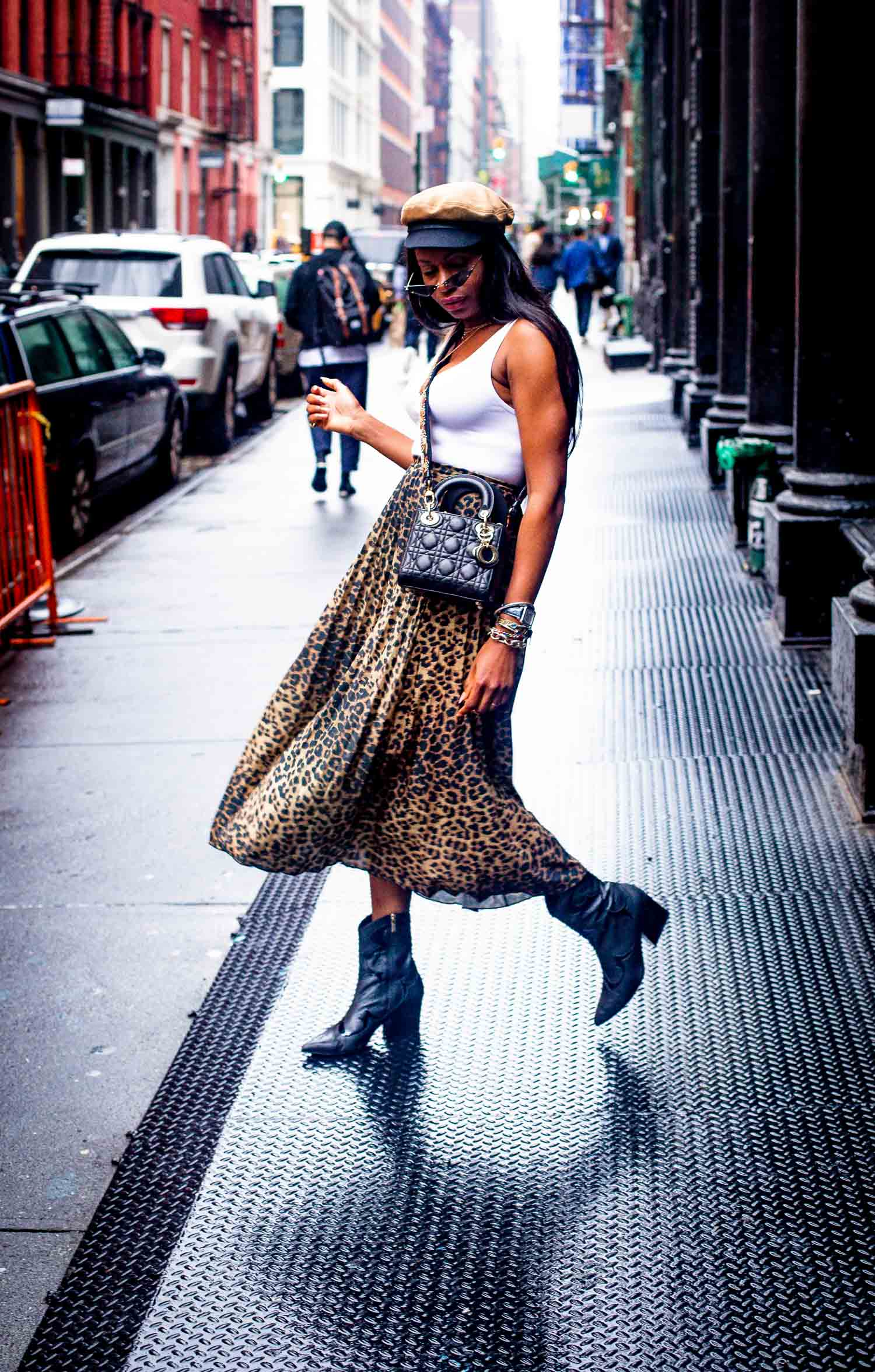 Atlanta fashion blogger Monica Awe-Etuk shows you how to wear the new leopard. Monica wearing white theory tubular tank top, asos leopard midi skirt, tibi cowboy boots, rag and bone cap, Christian Dior mini lady Dior and floral strap.