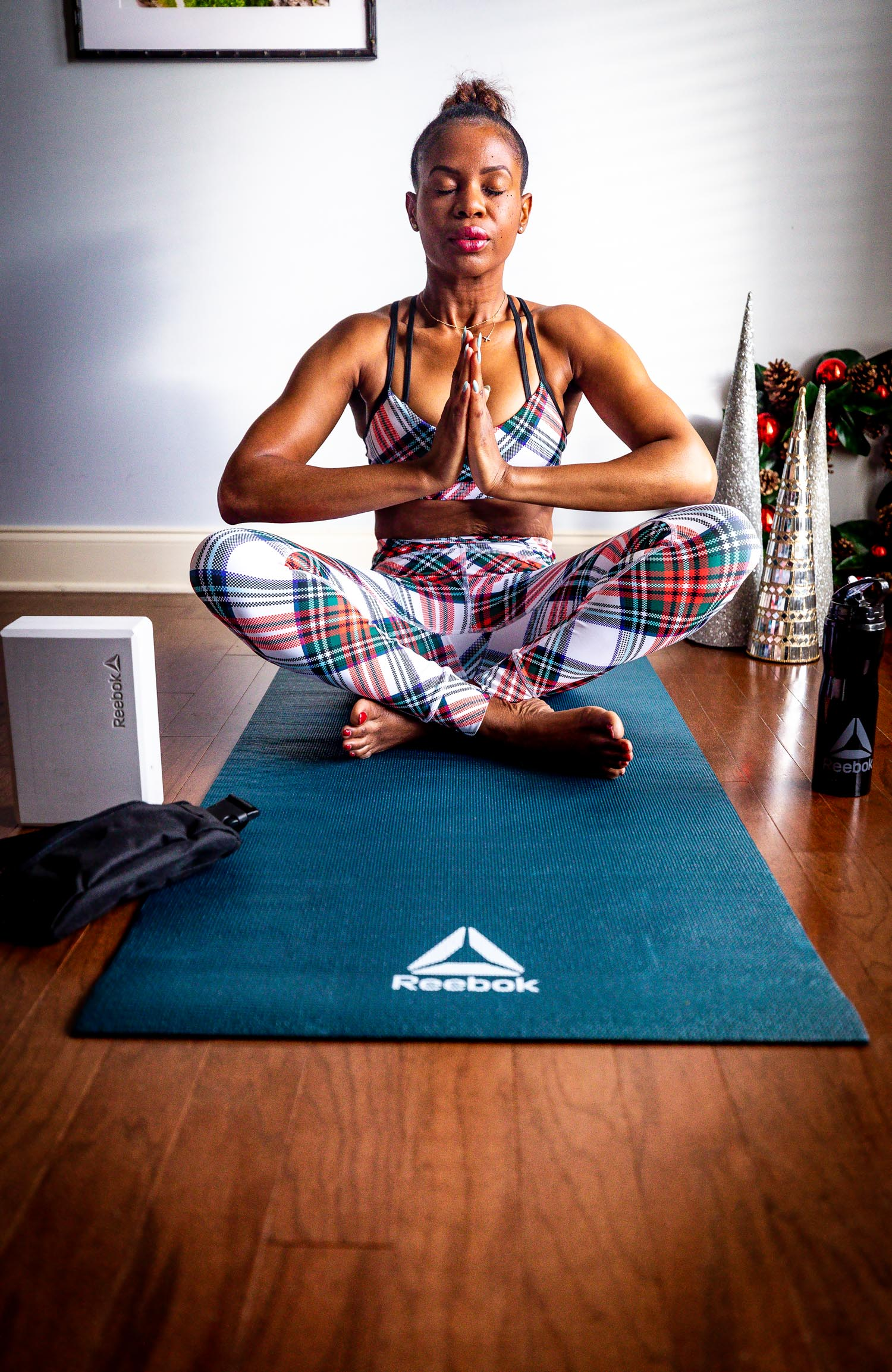Atlanta Lifestyle Blogger Monica Awe Etuk Wearing Reebok Plaid Leggings And Sports Bra Reebok Yoga Mat Yoga Block And Reebok Water Bottle For The Holiday 15 Awed By Monica