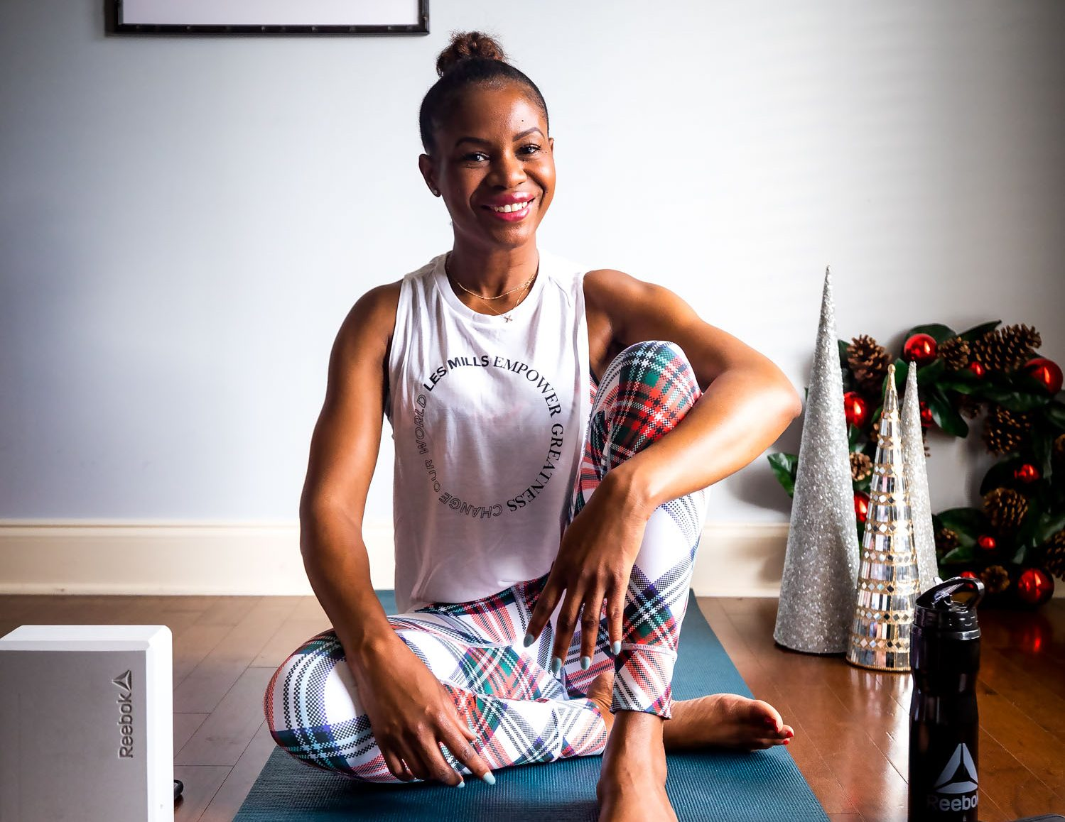 How Atlanta lifestyle blogger Monica Awe-Etuk will achieve minimum stress during the holidays. wearing reebok plaid leggings, and sports bra. Reebok yoga mat, yoga block and reebok water bottle for the holiday