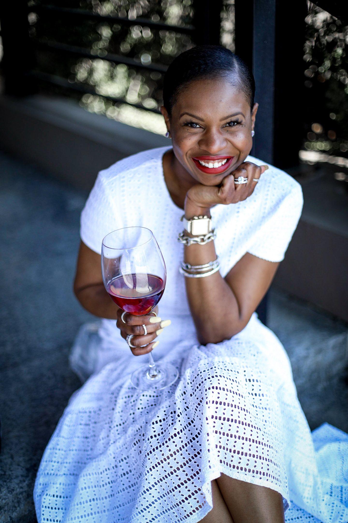 Atlanta fashion blogger Monica Awe-Etuk in a white eyelet dress toasting to the new year