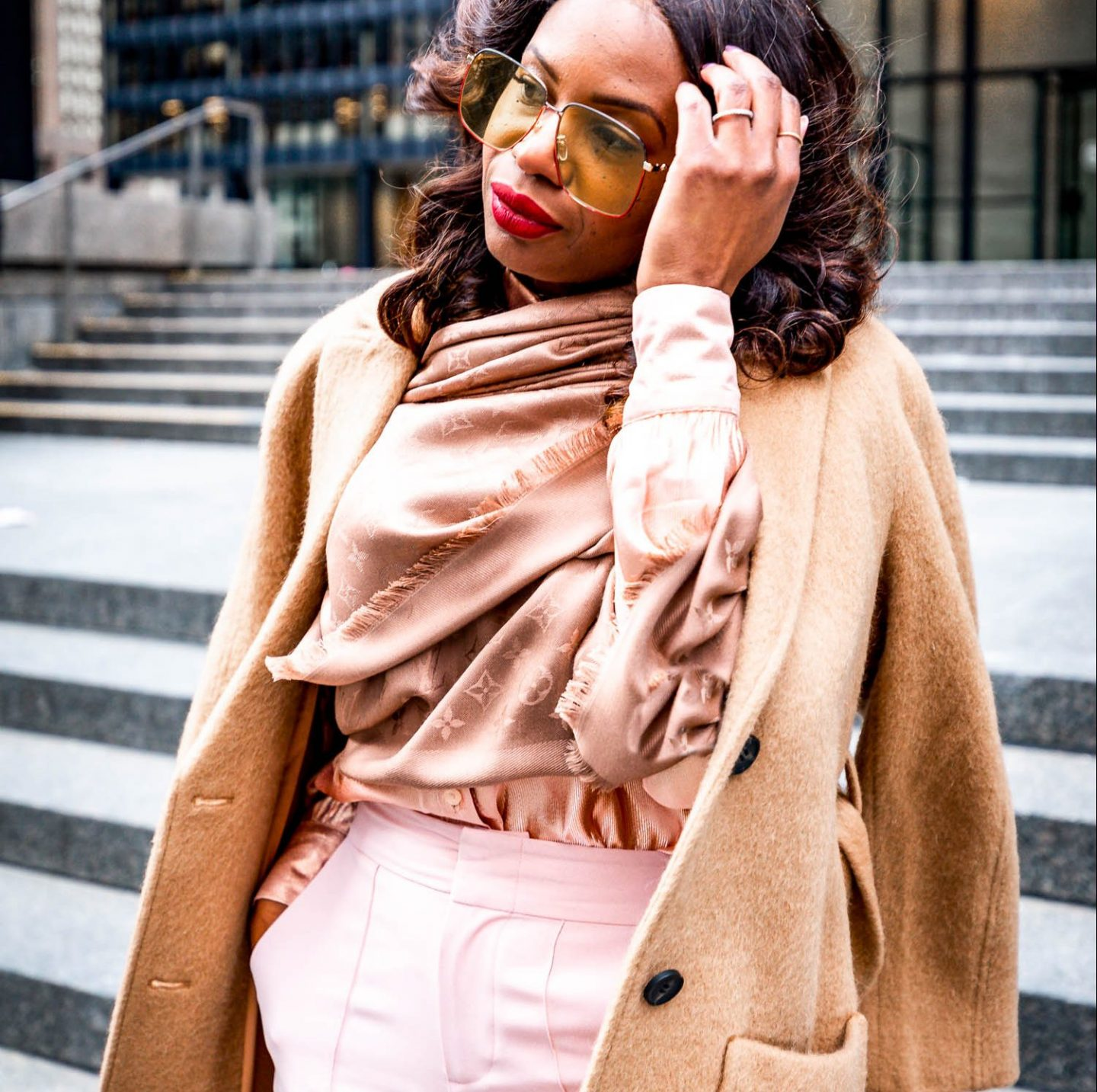 Atlanta blogger Monica Awe-Etuk wearing a Louis Vuitton scarf, camel coat, square gucci oversized sunglasses, blush alice and oliva pants and valentino rockstud pumps shot downtown toronto