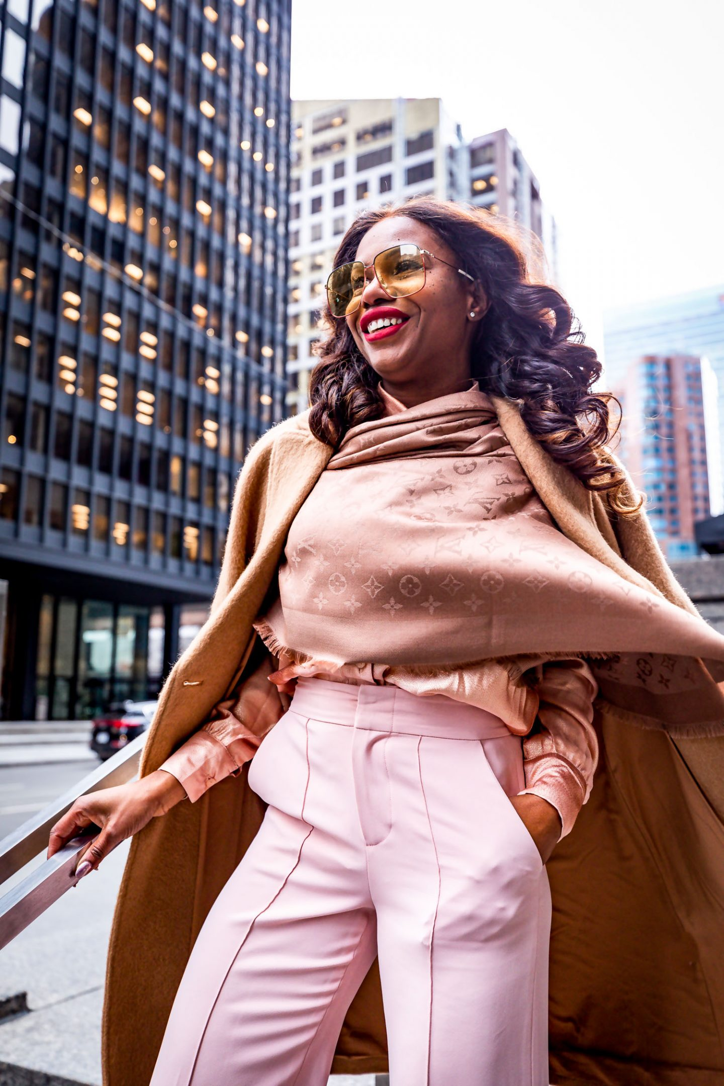 Atlanta blogger Monica Awe-Etuk wearing a Louis Vuitton scarf, camel coat, square gucci oversized sunglasses, blush alice and oliva pants and valentino rockstud pumps shot downtown toronto