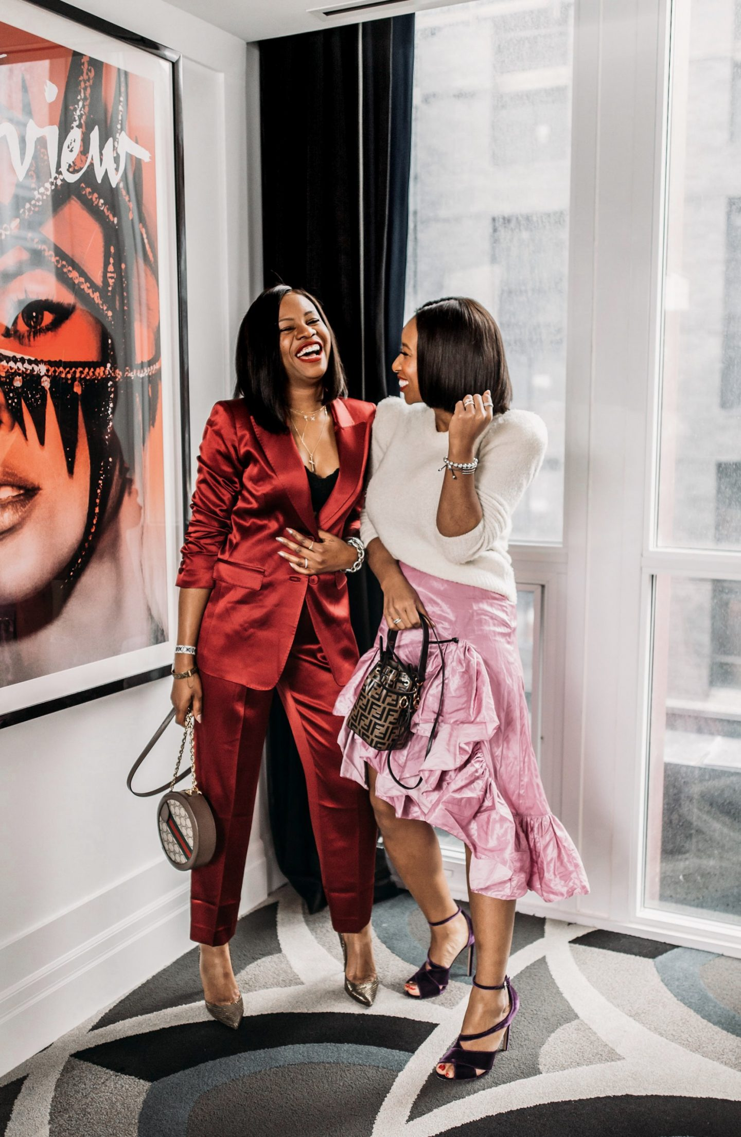 Atlanta blogger Monica Awe-Etuk wearing a silk red suit, christian louboutin metallic pumps, and gucci ophidia mini gg round shoulder bag at the Bisha hotel in toronto with toronto blogger Toronto Shay wearing ivory sweater and lilac midi skirt and fendi bucket bag tells you everything you need to know about the suit trend and how to style suits