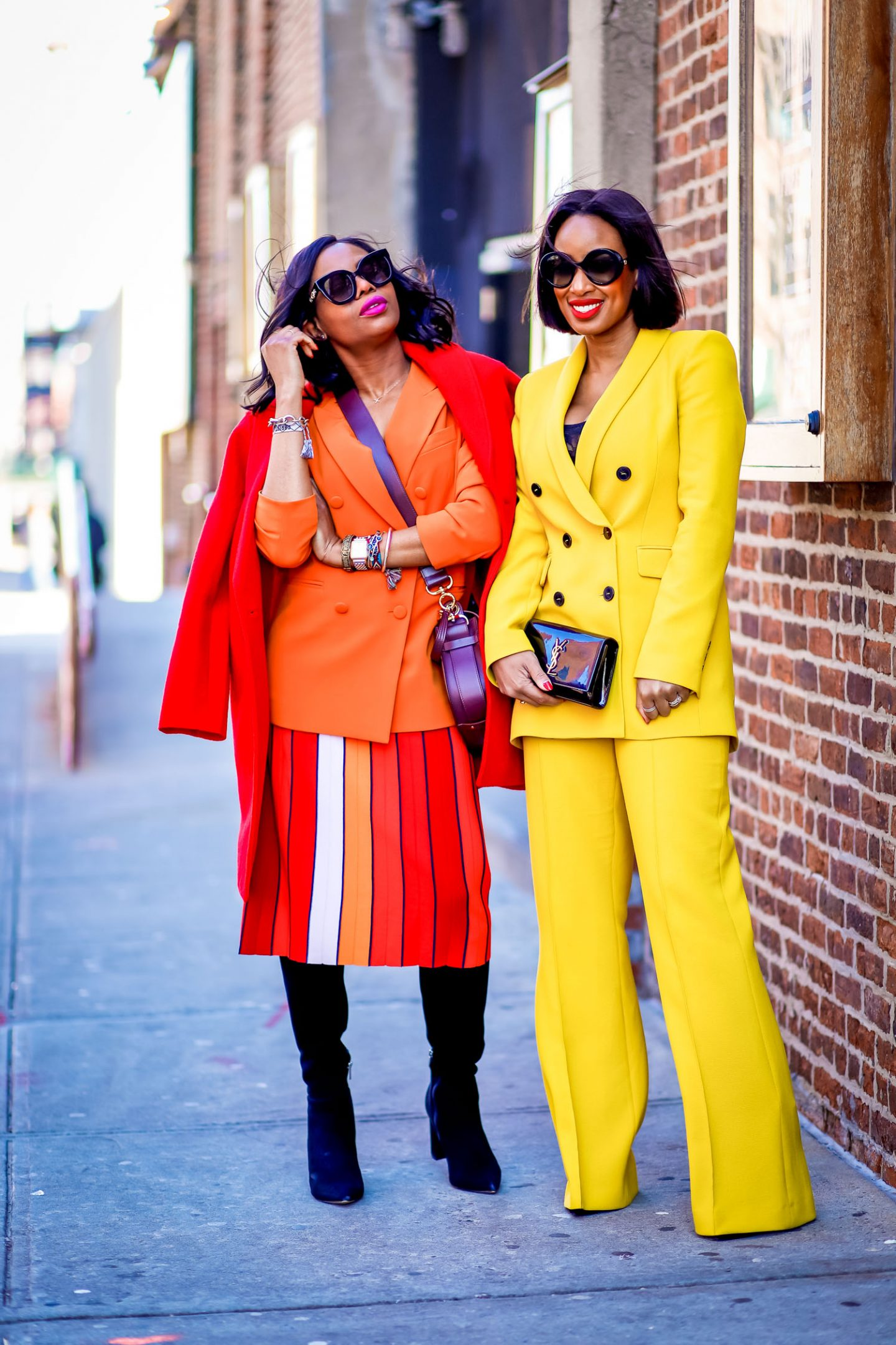 Atlanta blogger Monica Awe-Etuk wearing & Other Stories coral/ orange blazer, multi-color tory burch midi skirt, marc fisher black suede knee-high boots, chloe tess bag, gucci black cat-eye sunglasses and toronto blogger Toronto Shay wearing zara yellow suit during nyfw tells you everything you need to know about the suit trend and how to style suits