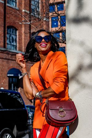 Atlanta lifestyle blogger Monica Awe-Etuk wearing & Other Stories orange blazer and tory burch midi skirt, marc fisher black knee-high boots and chloe tess saddle bag, gucci sunglasses during nyfw-3