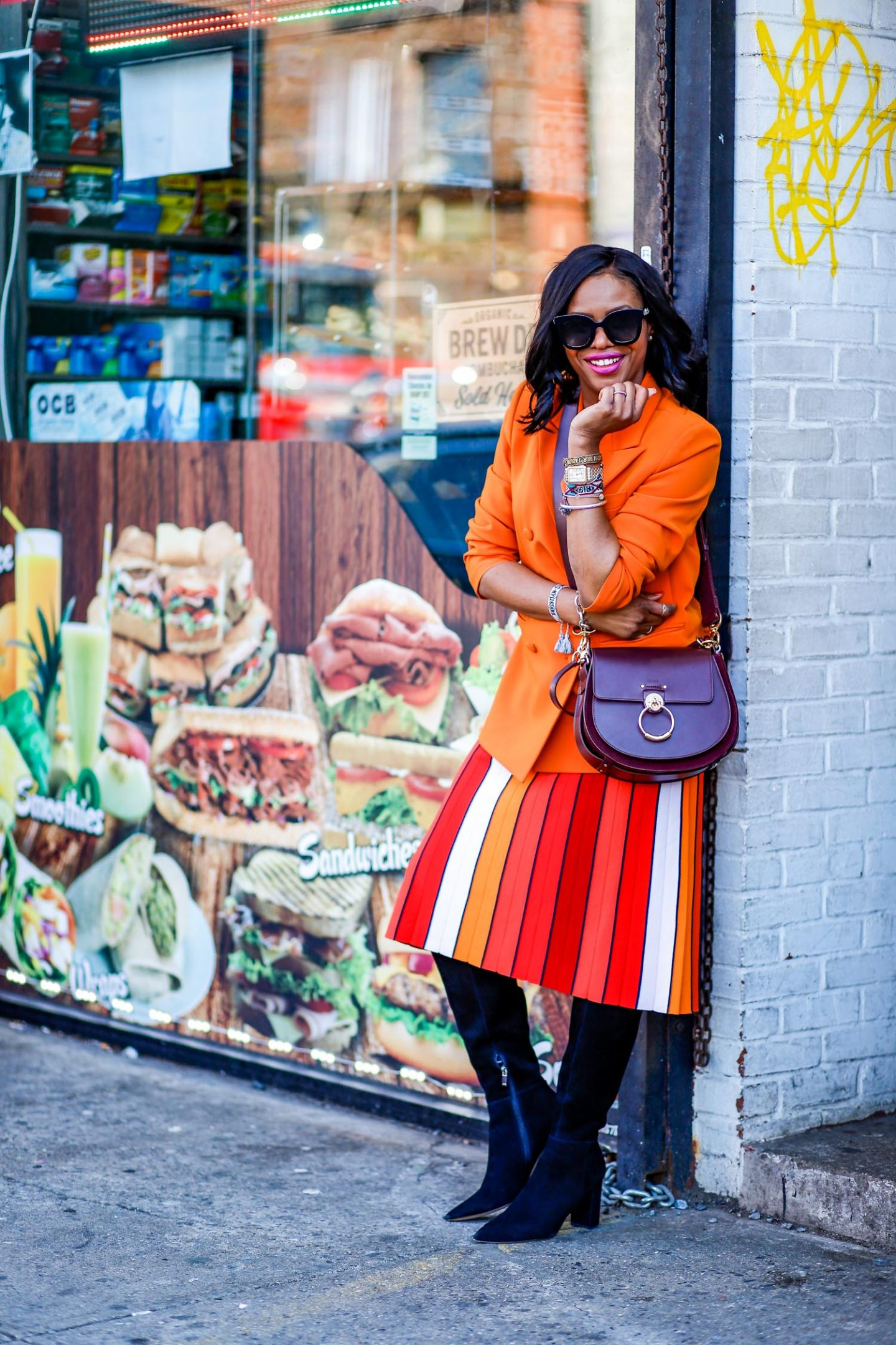 Atlanta blogger Monica Awe-Etuk wearing & Other Stories coral/ orange blazer, multi-color tory burch midi skirt, marc fisher black suede knee-high boots, chloe tess bag, gucci black cat-eye sunglasses during nyfw tells you everything you need to know about the suit trend and how to style suits