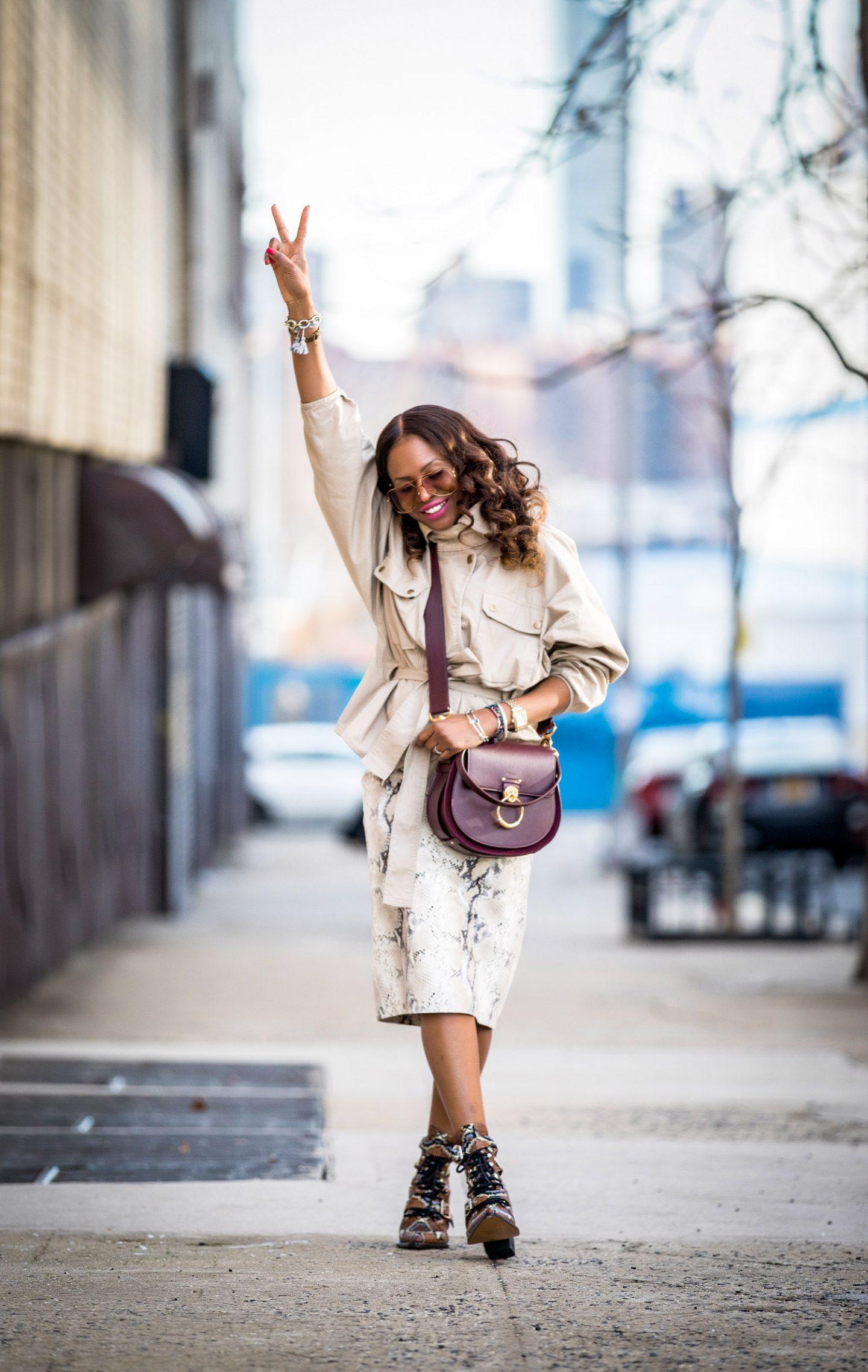 Atlanta lifestyle blogger Monica Awe-Etuk wearing a belted cargo jacket with a lafayette snakesin skirt and chloe snake boots. safari jacket belted jacket, Chloe tess bag, chloe bag, chloe sunglasses, chloe girl, utility trend, utility chic