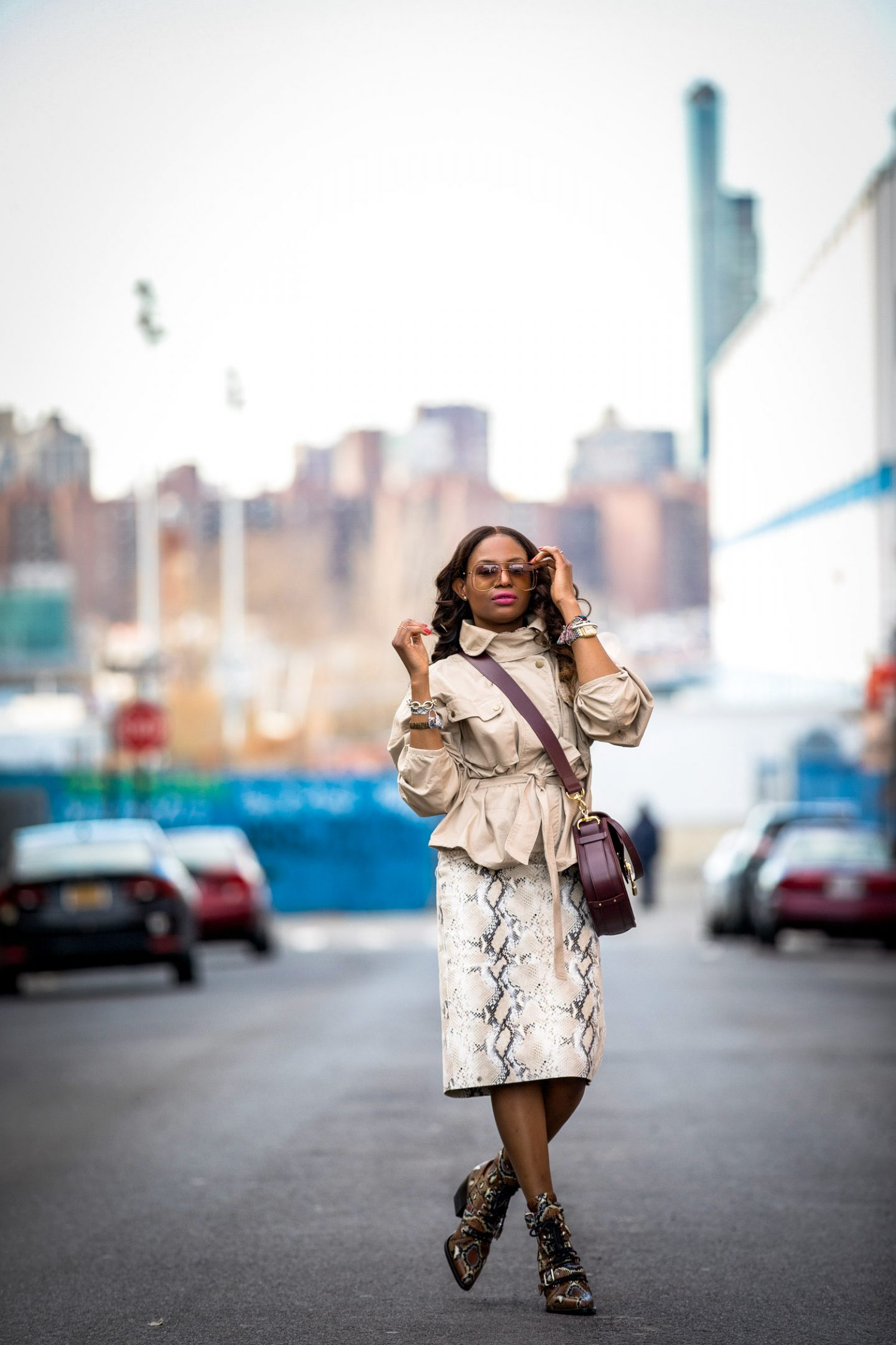 Atlanta lifestyle blogger Monica Awe-Etuk wearing a belted cargo jacket with a lafayette snakesin skirt and chloe snake boots. safari jacket belted jacket, Chloe tess bag, chloe bag, chloe sunglasses, chloe girl, utility trend, utility chic