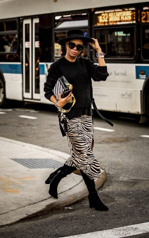 Atlanta lifestyle blogger Monica Awe-Etuk wearing a zebra slit skirt, black suede knee-high boots, black sweater, black fedora, off-white bag, black gucci sunglasses in new york city
