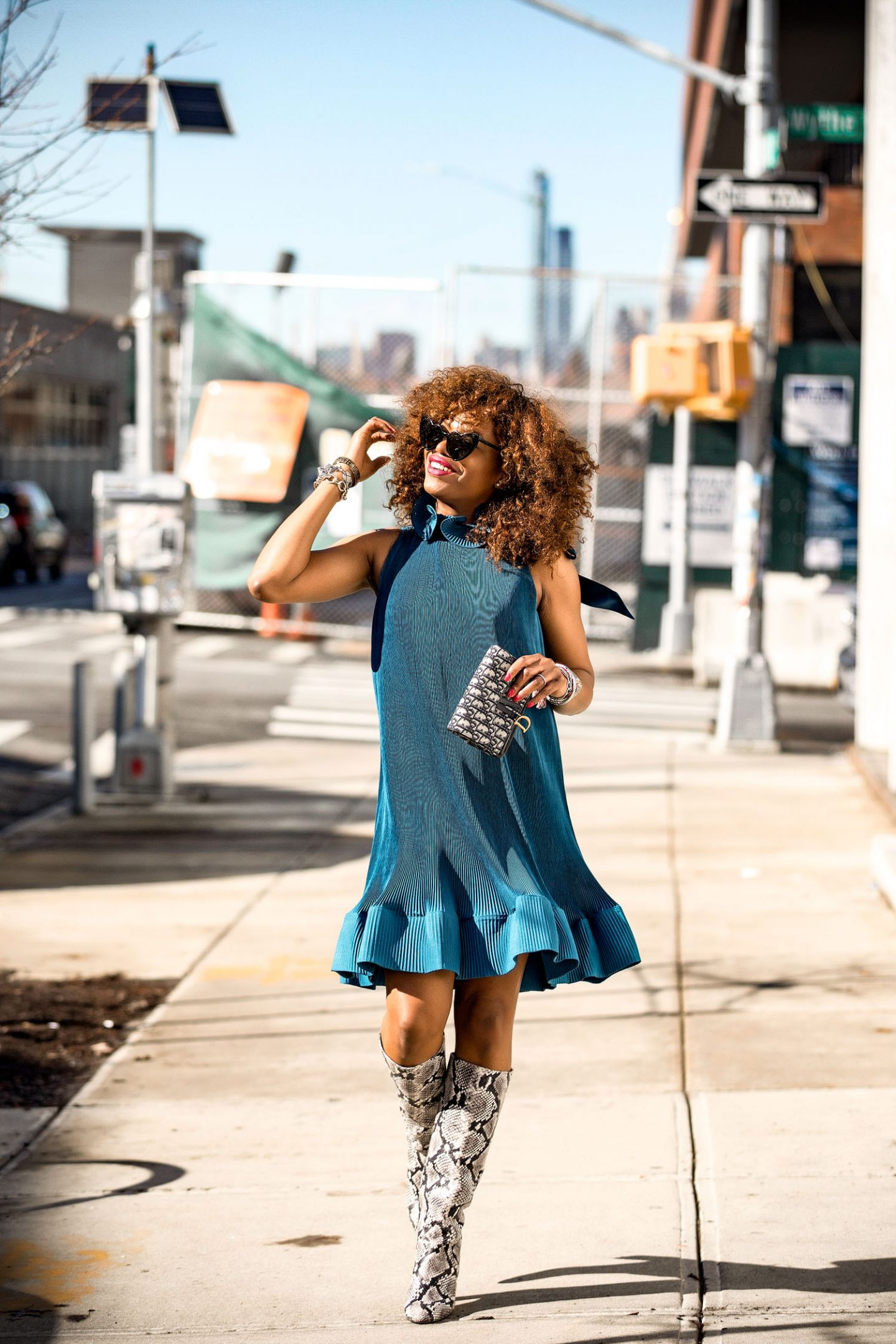 Atlanta Fashion blogger Monica Awe-Etuk wearing a blue tibi pleated dress, jcrew snake boots, ysl heart sunglasses, dior oblique belt bag worn as a clutch
