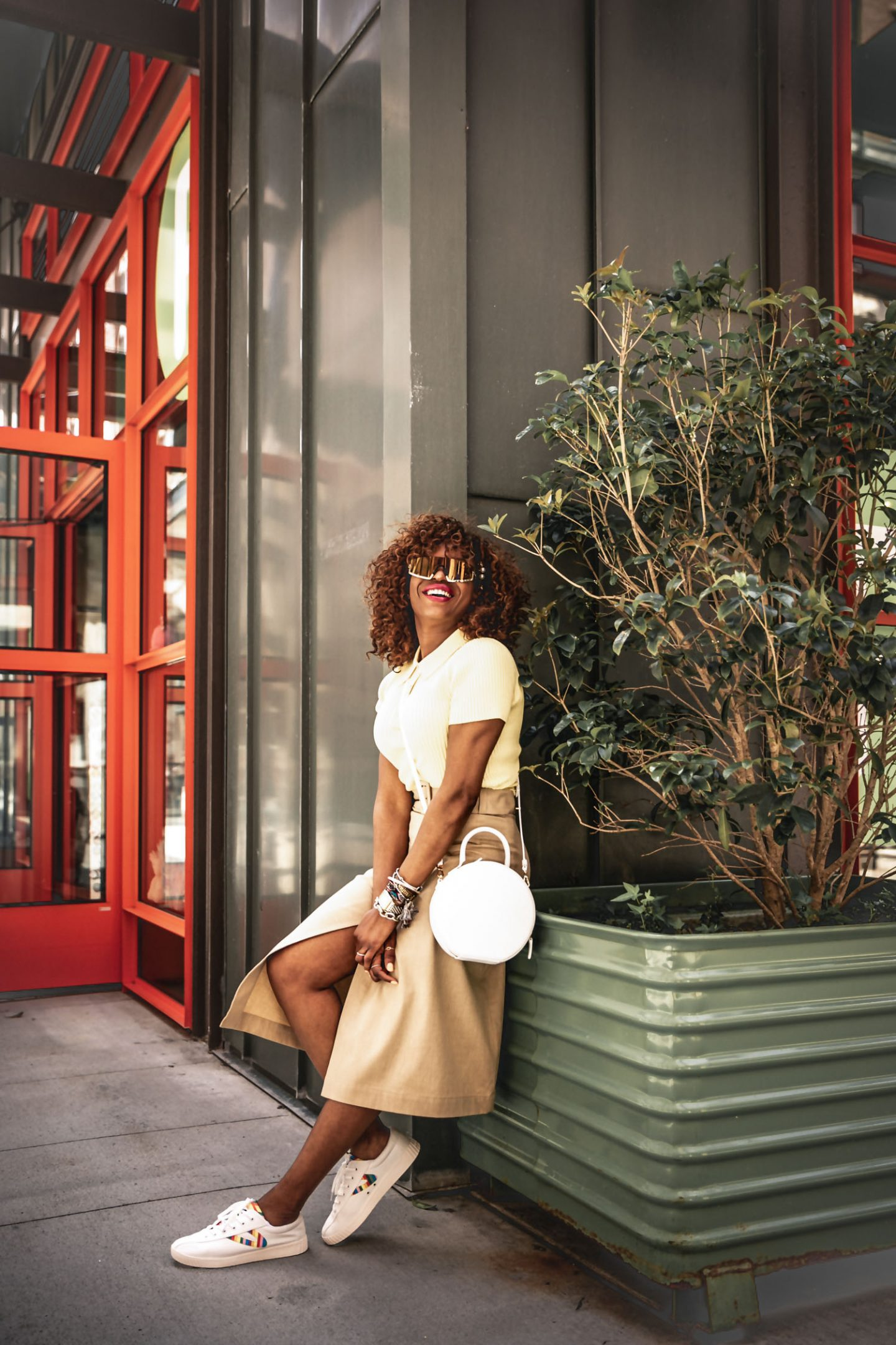 Atlanta fashion blogger Monica Awe-Etuk wearing & Other Stories yellow knit polo top, beige wrap skirt, Tretorn sneakers, white bag, and futuristic sunglasses