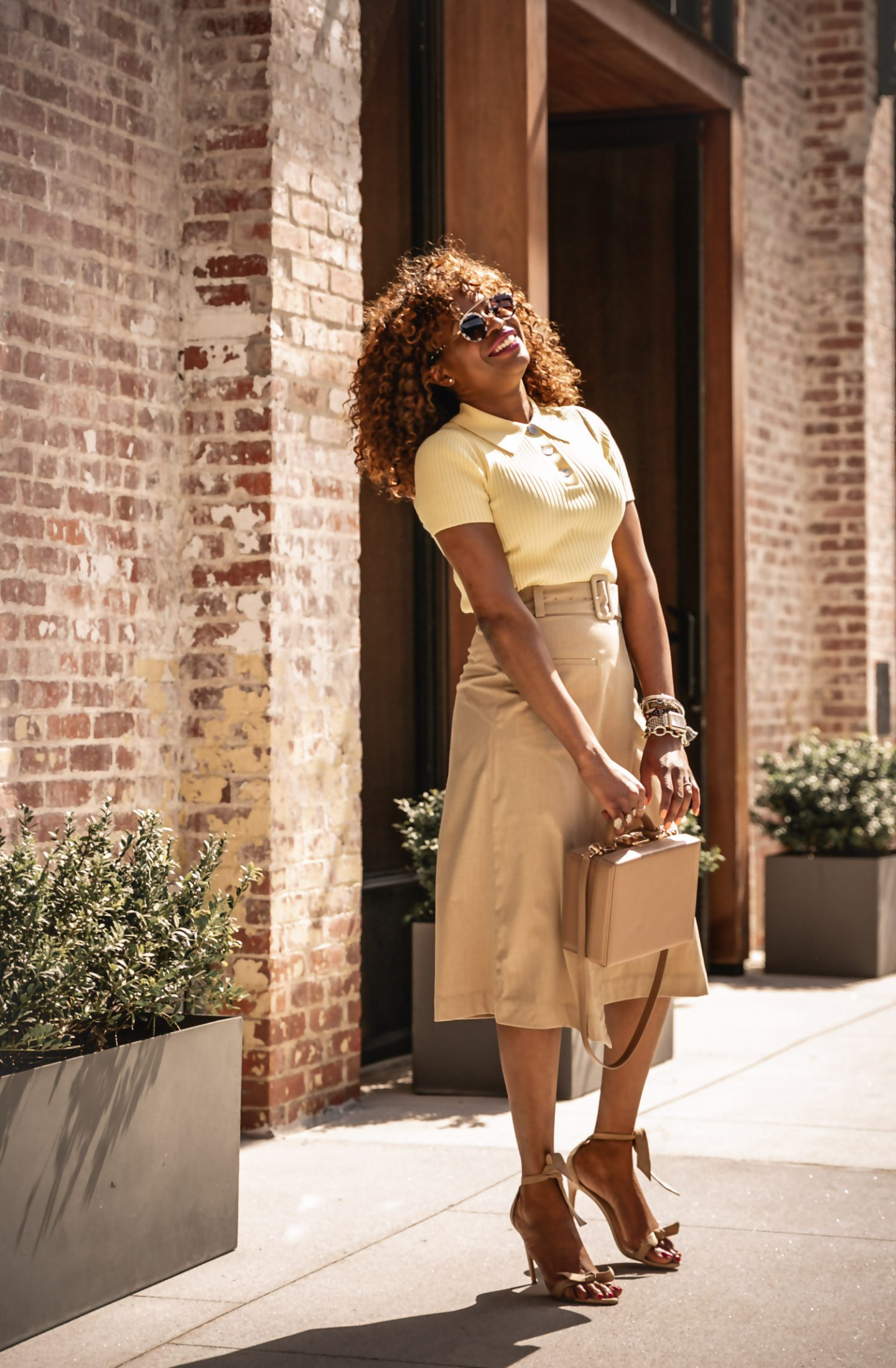 The best easter outfit. Atlanta fashion blogger Monica Awe-Etuk wearing & Other Stories yellow knit polo top, beige wrap skirt, alexandria birman tie-front sandals and round sunglasses.