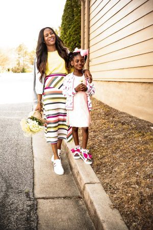 Atlanta fashion blogger Monica Awe-Etuk creates mommy and me spring trends wearing spring trends from walmart. yellow sweatshirt, multi-color slit midi skirt, white sneakers from ev1, denim jacket with love detail by evi-9