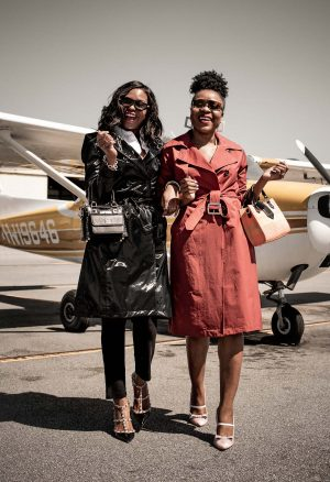 Atlanta fashion bloggers Monica Awe-Etuk and Titi Sogunro both wearing spring trench coats to travel, hartmanns luggage, mark and graham carry-on, futuristic sunglasses at private airport, debunking travel myths and travel tips
