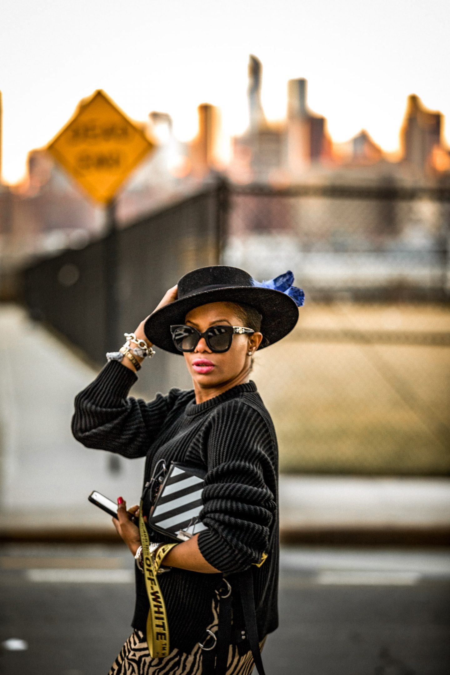 How to wear a slit skirt everyday. Atlanta lifestyle blogger Monica Awe-Etuk wearing a zebra slit skirt, black suede knee-high boots, black sweater, black fedora, off-white bag, black gucci sunglasses in new york city