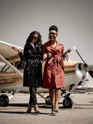 Atlanta fashion bloggers Monica Awe-Etuk and Titi Sogunro both wearing spring trench coats to travel, hartmanns luggage, mark and graham carry-on, futuristic sunglasses at private airport .Travel Myths Debunked by travel expert.
