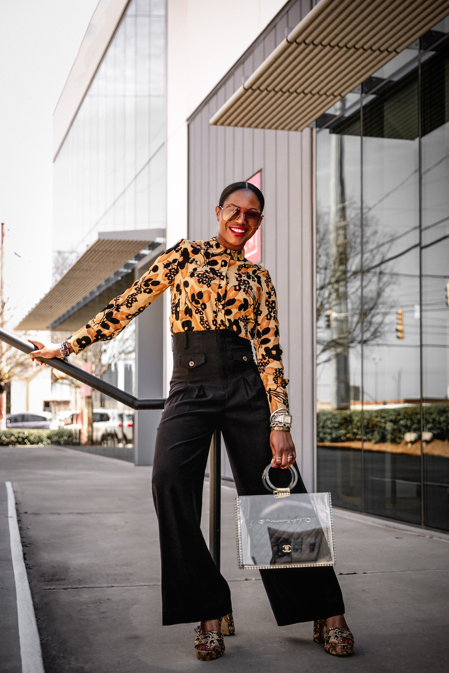 Atlanta fashion blogger Monica Awe-Etuk wearing & other stories dark floral blouse, black high-waist pants, tory burch platform sandals, oversized chloe sunglasses, clear bag and chanle 2.55 classic in cowhide. Shows you how to wear black pants in the spring and summer.