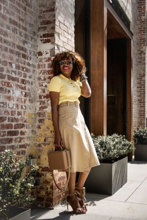 Atlanta fashion blogger Monica Awe-Etuk wearing & Other Stories yellow knit polo top, beige wrap skirt, alexandria birman tie-front sandals and round sunglasses, white tretor sneakers and white bag. what to wear for easter