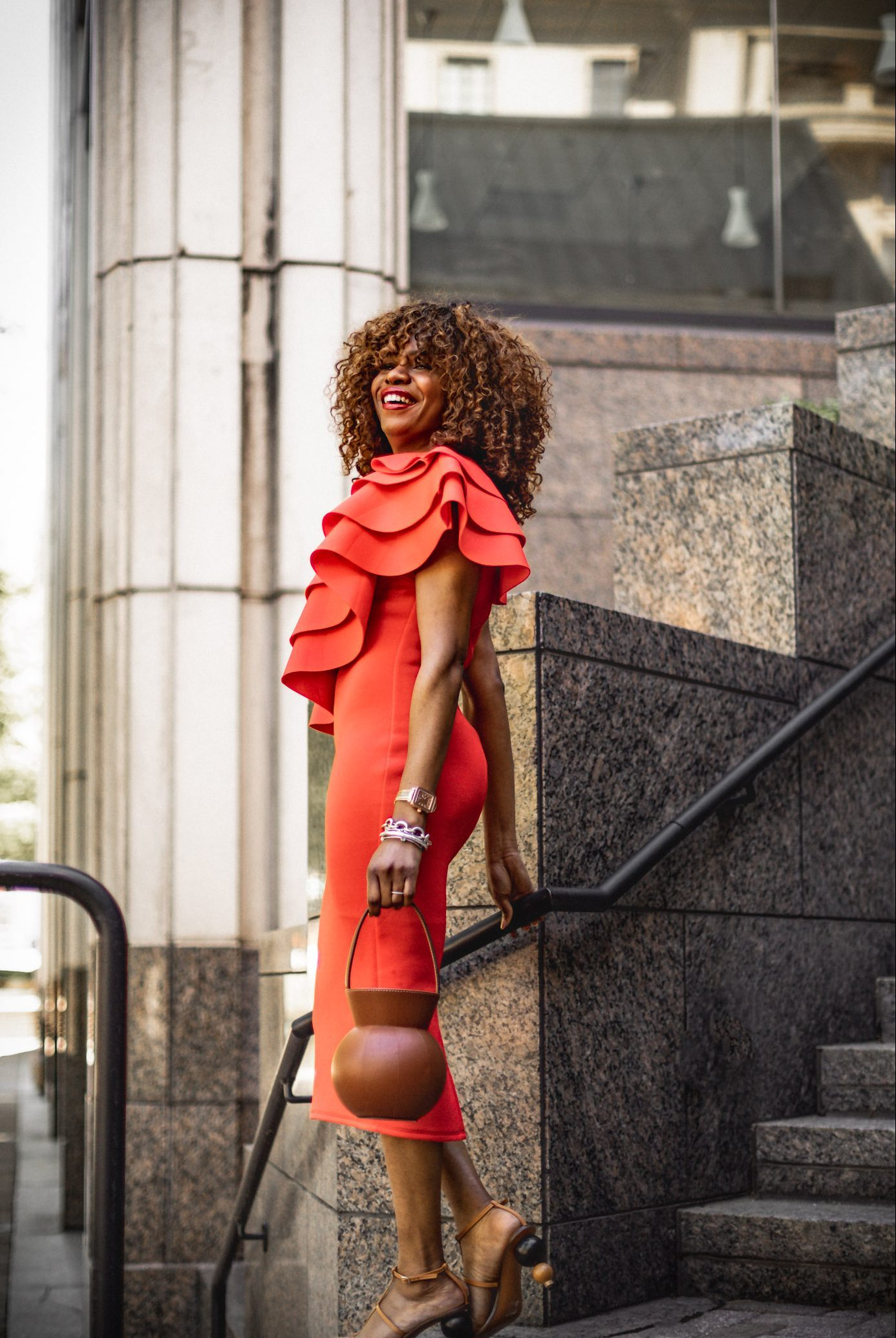 Atlanta fashion blogger Monica Awe-Etuk wearing orange dress for mother's Day. What to wear for Mother's Day. The perfect mothers day outfit featuring a orange scuba midi dress, staud brown round bag, cult gaia brown sandals
