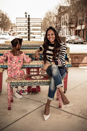blogger Monica Awe-Etuk wearing spring trends from walmart. stripe sweater, boyfriend jeans, cult gaia white mules, gucci square sunglasses with her daughter wearing girls jumpsuit from walmart and jojo siwa sneakers