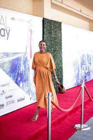 Atlanta blogger Monica Awe-Etuk wearing co orange midi dress, Rejina Pyo sandals and staud bucket bag