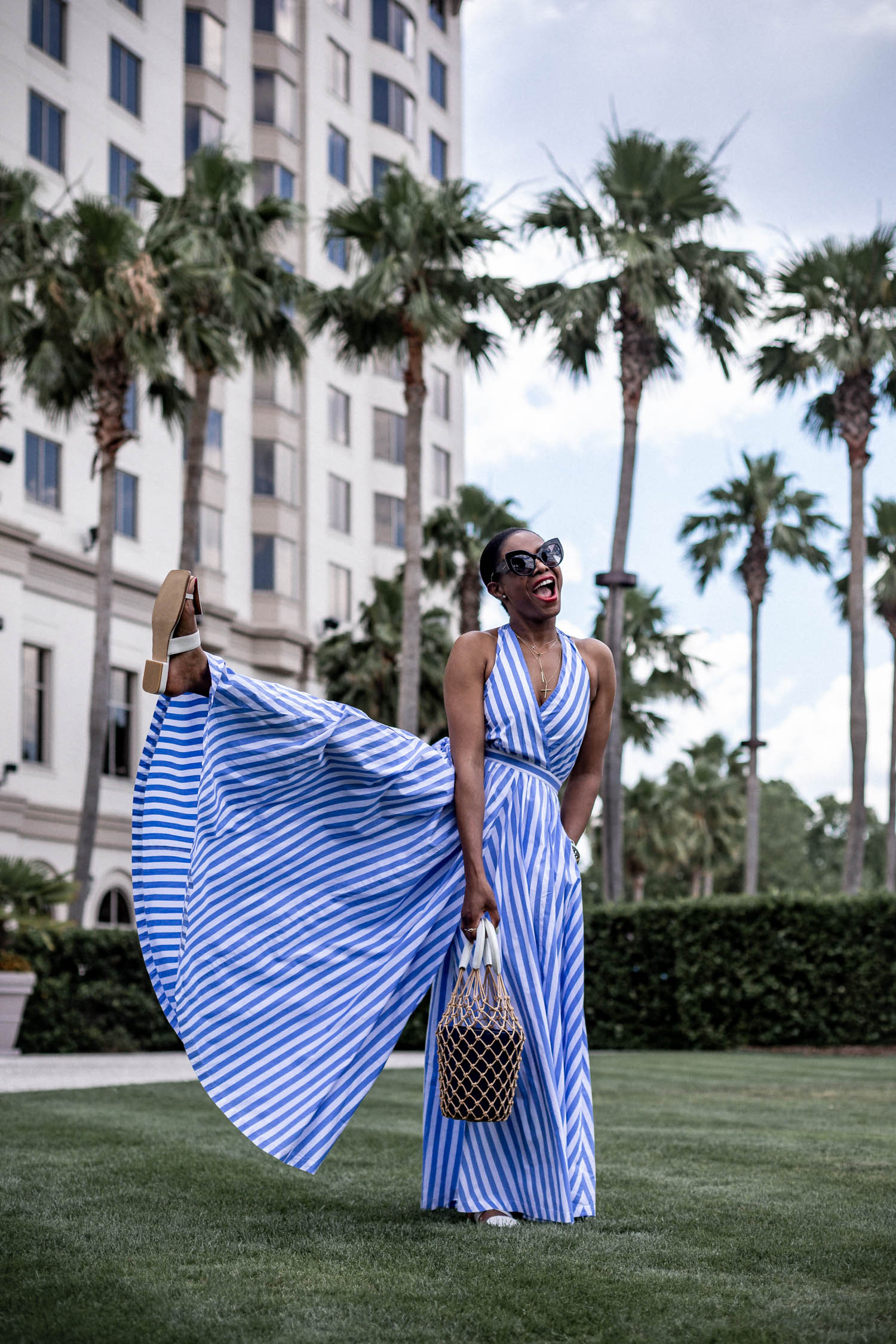 Atlanta blogger Monica Awe-Etuk wearing jcrew wide leg halter jumpsuit, white sandals, d&g black cat eye sunglasses and staud bag