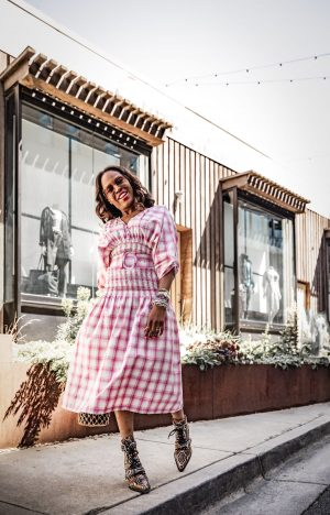 Atlanta blogger Monica Awe-Etuk wearing pink plaid dress by Nicholas Smocked Panel Dress and chloe snake boots and oversized aviator sunglasses, staud Moreau Bag