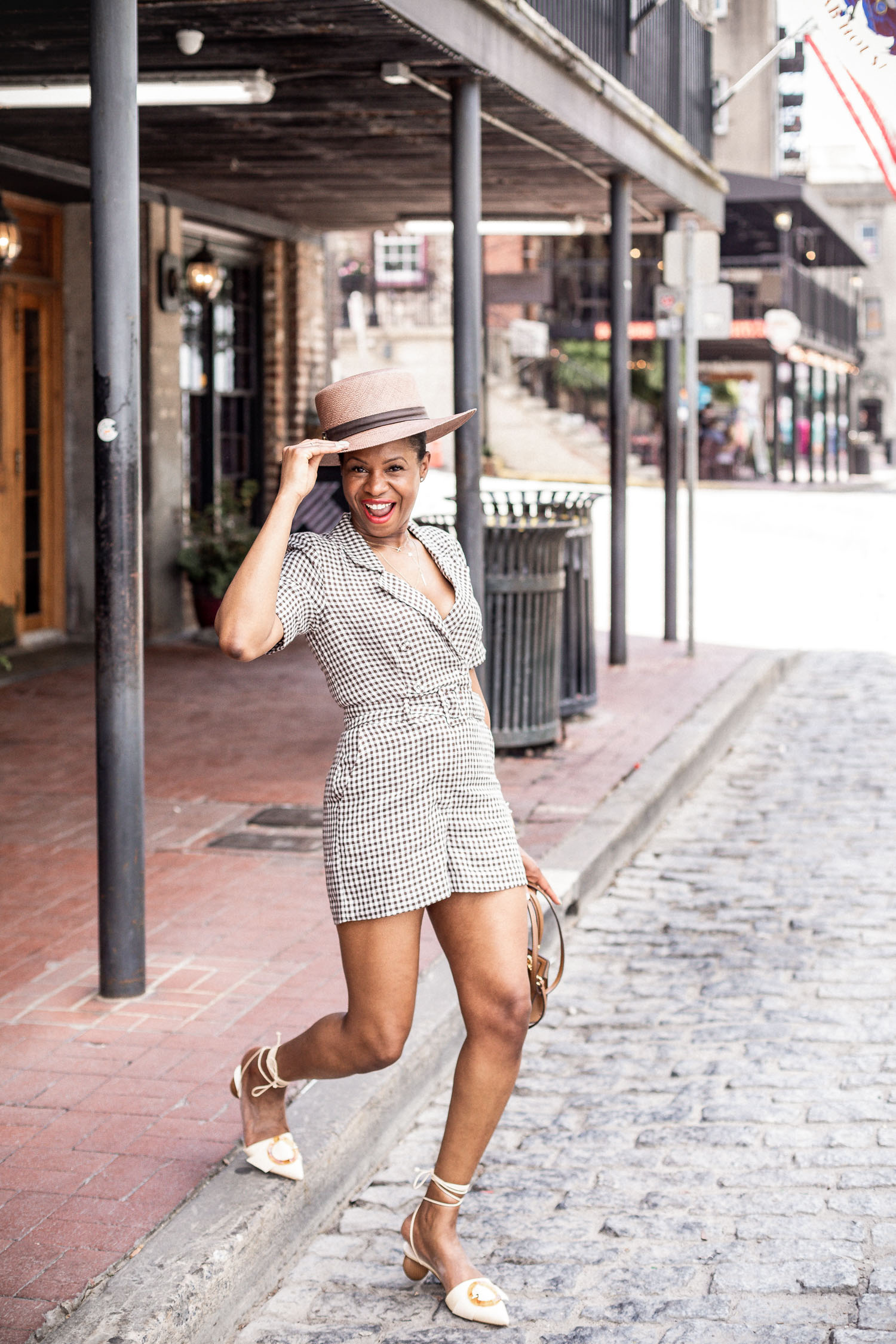 Atlanta blogger Monica Awe-Etuk wearing & other stories brown plaid romper, cult gaia shoes, tory burch kelly bag, and brown hat
