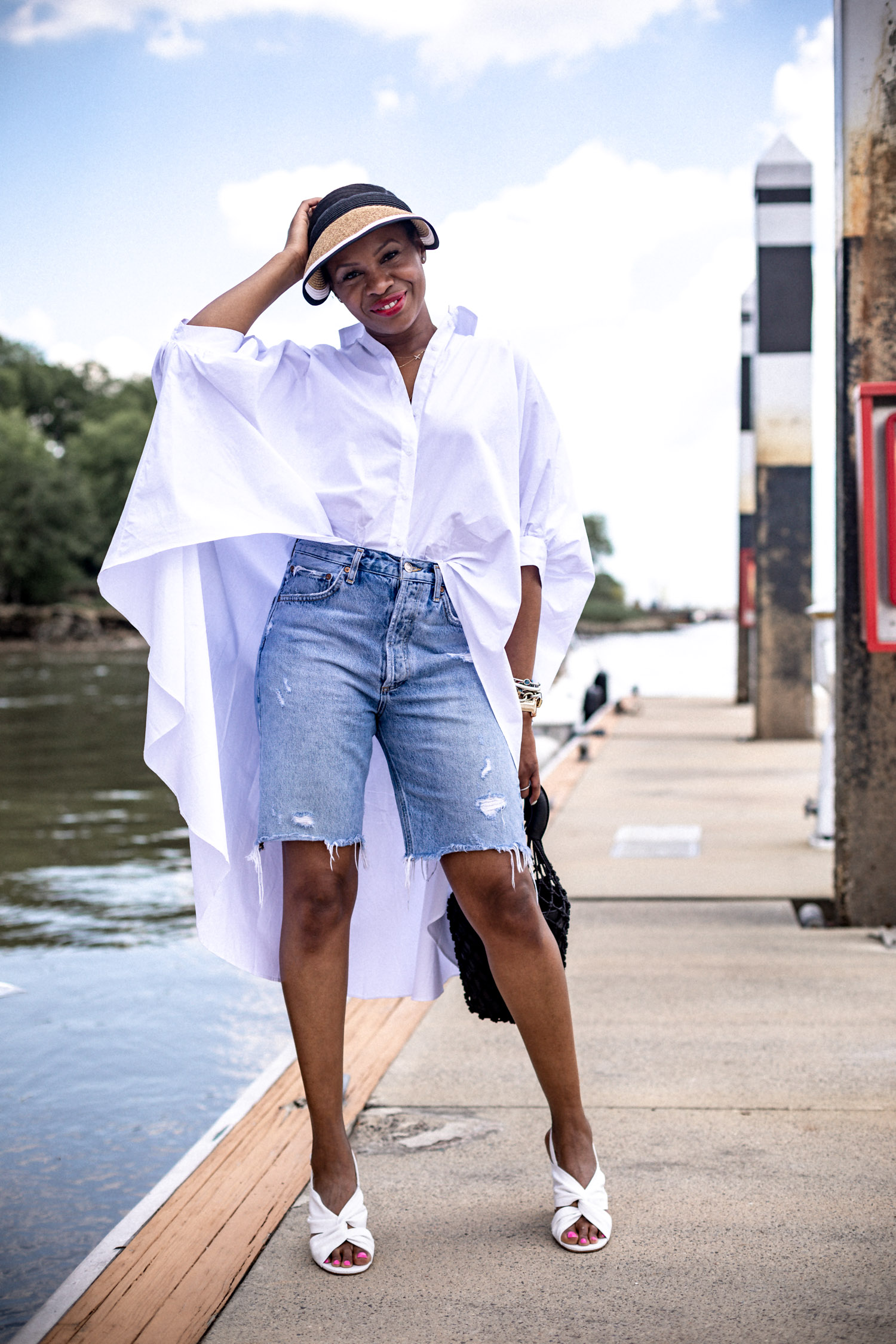 Atlanta Blogger Monica Awe Etuk Wearing White High Low Shirt White Sandals Visor From Nordstrom Rack And Staud Bag And High Waist Bermuda Shorts 5 Awed By Monica