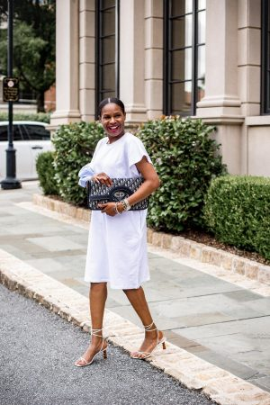 Atlanta fashion and lifestyle blogger Monica Awe-etuk wearing a WHBM white t-shirt dress with strip details, white sandals, and dior oblique over-sized clutch, dior oblique fold over clutch.