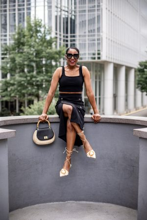 Atlanta fashion and lifestyle blogger Monica wearing express black crop top and midi skirt, cult gaia buckle shoes, gucci square sunglasses, bamboo handle straw bag