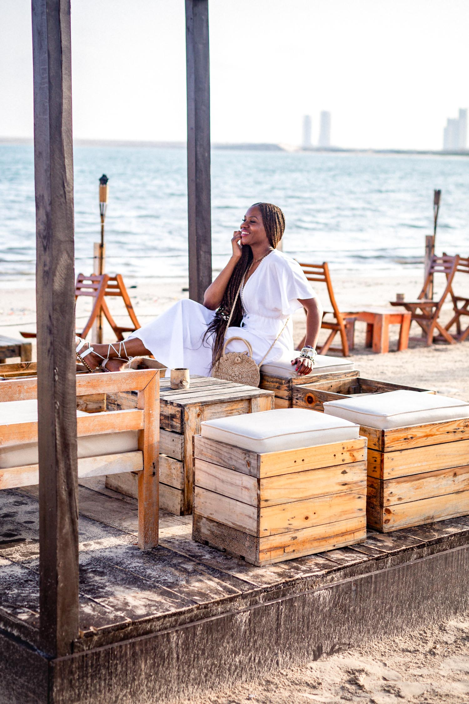 Atlanta fashion and lifestyle blogger Monica wearing walmart white midi dress, straw cross body bag, and white galdiator sandals at moist beach in lagos nigeria, what to wear on a tropical getaway