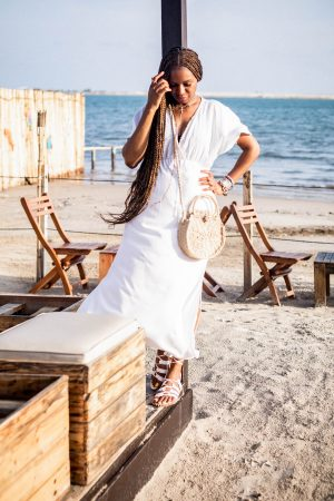 Atlanta fashion and lifestyle blogger Monica wearing walmart white midi dress, straw cross body bag, and white galdiator sandals at moist beach in lagos nigeria, what to wear on a tropical getaway, atlanta blogger shares her travel experience visiting Nigeria West Africa, travel post, travel blogger