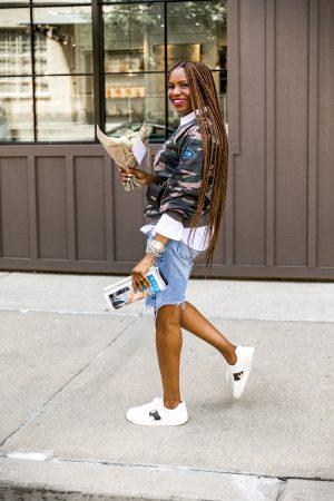 Atlanta fashion and lifestyle blogger monica awe-etuk wearing walmart camouflage sweatshirt, white shirt, denim biker shorts, white sneakers with camouflage details, jacquemus belt bag, long hair, long braids, agolde denim shorts