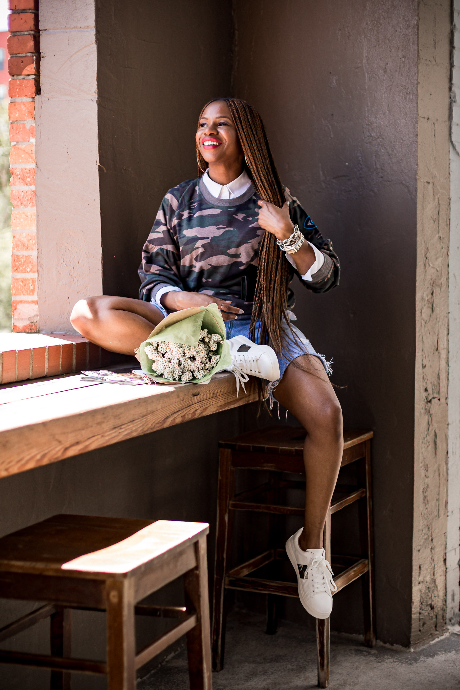 Atlanta fashion and lifestyle blogger monica awe-etuk wearing walmart camouflage sweatshirt, white shirt, denim biker shorts, white sneakers with camouflage details, jacquemus belt bag, long hair, long braids, agolde denim shorts, fall prints