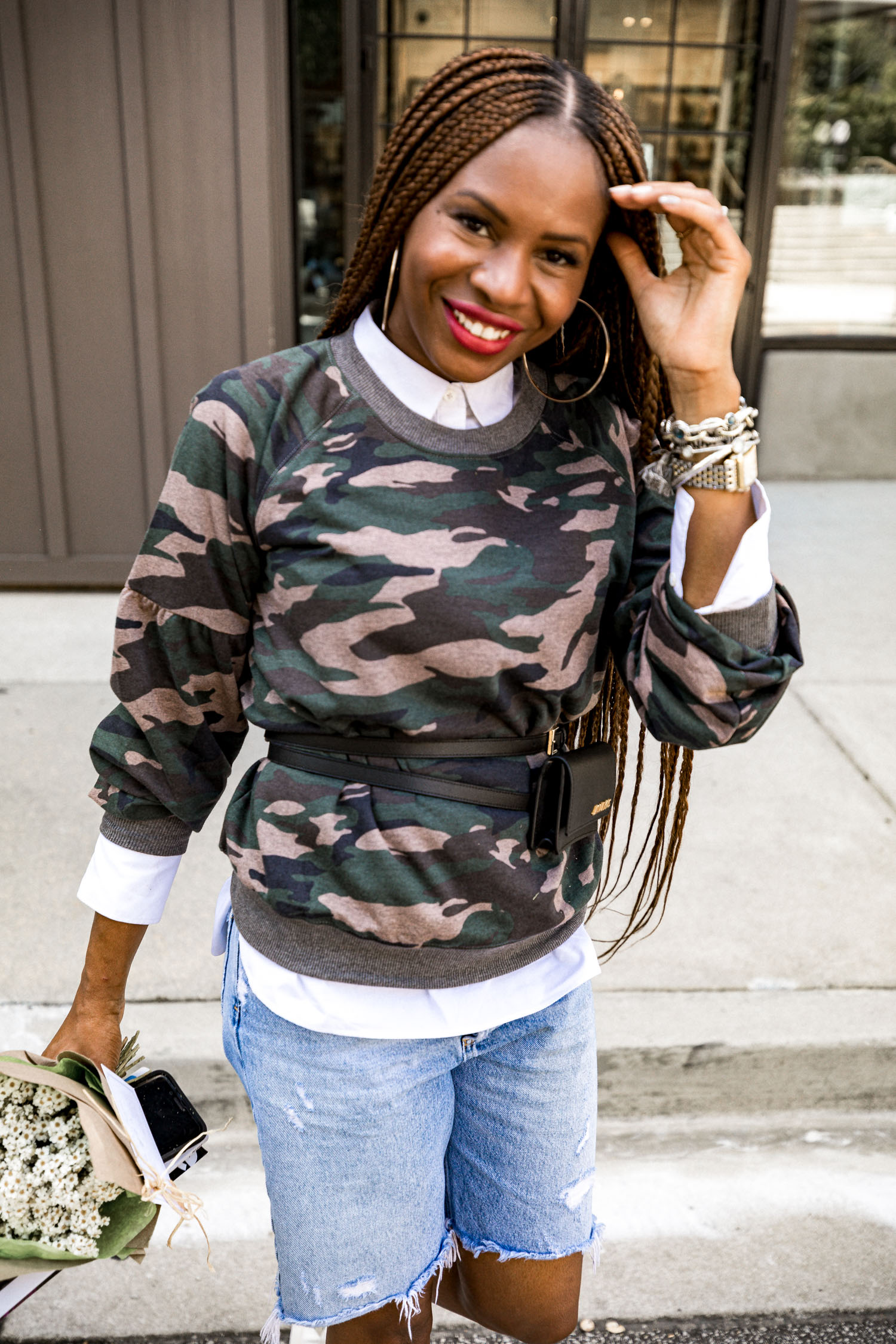 Atlanta fashion and lifestyle blogger monica awe-etuk wearing walmart camouflage sweatshirt, white shirt, denim biker shorts, white sneakers with camouflage details, jacquemus belt bag, long hair, long braids, agolde denim shorts, fall prints, top fall prints, fashion trends