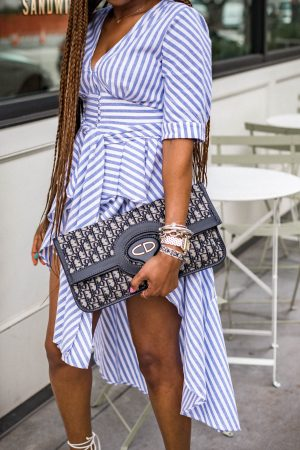 dior oblique bag, Atlanta fashion and lifestyle blogger monica wearing english factory high-low blue and white stripe top with white denim shorts, english factory, agold jeans, white jeans, white denim, stripe top, stripes, white sandals, j.crew sandals, long braids, box braids, dior bag, dior cluthc, dior oblige bag, atlanta blogger, top atlanta blogger