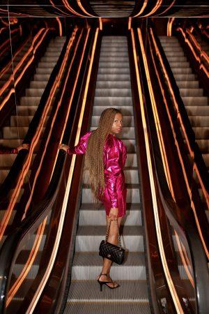 top atlanta blogger monica awe-etuk wearing rotate pink dress, bottega stretch sandals and chanel bag, metallic dress, bottega venetta, nyfw, street style, public hotel, chanel 2.55 bag gold details, how to style rotate dress, long braids, black girls at new york fashion week, public hotel, public hotel new york, public hotel escalator