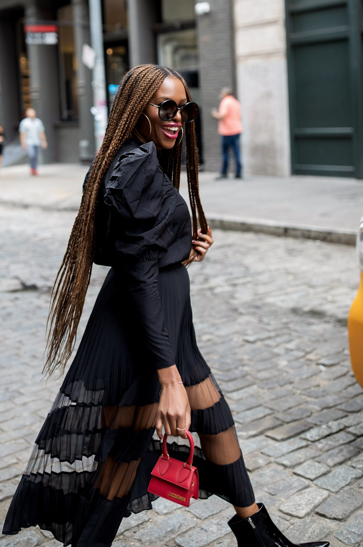 atlanta fashion blogger monica awe-etuk, nyfw, fashion trends, how to survive nyfw, street style, wearing other stories black puff sleeve top and black sheer midi skir, Jacquemus small bag, red bag, marc fischer boots, round sunglasses, croc boots, how to wear booties with a skirt, long braids, how to wear puff sleeves