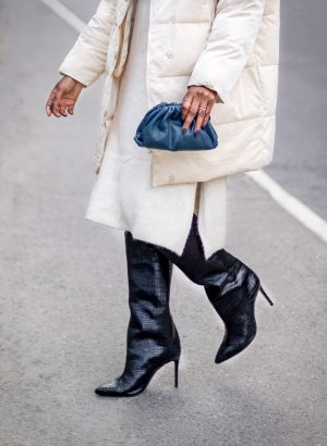 atlanta blogger wearing white puffer jacket, ivory sweater dress, how to style a puffer coat, how warm are puffer coats, why are puffer coats popular, why puffer coats are puffer, how to make a puffer coat chic, black boots, knee high boots, croc print boots, black boots, bottega clutch, bottega bag, how to style bottega bag, where to buy bottega bag