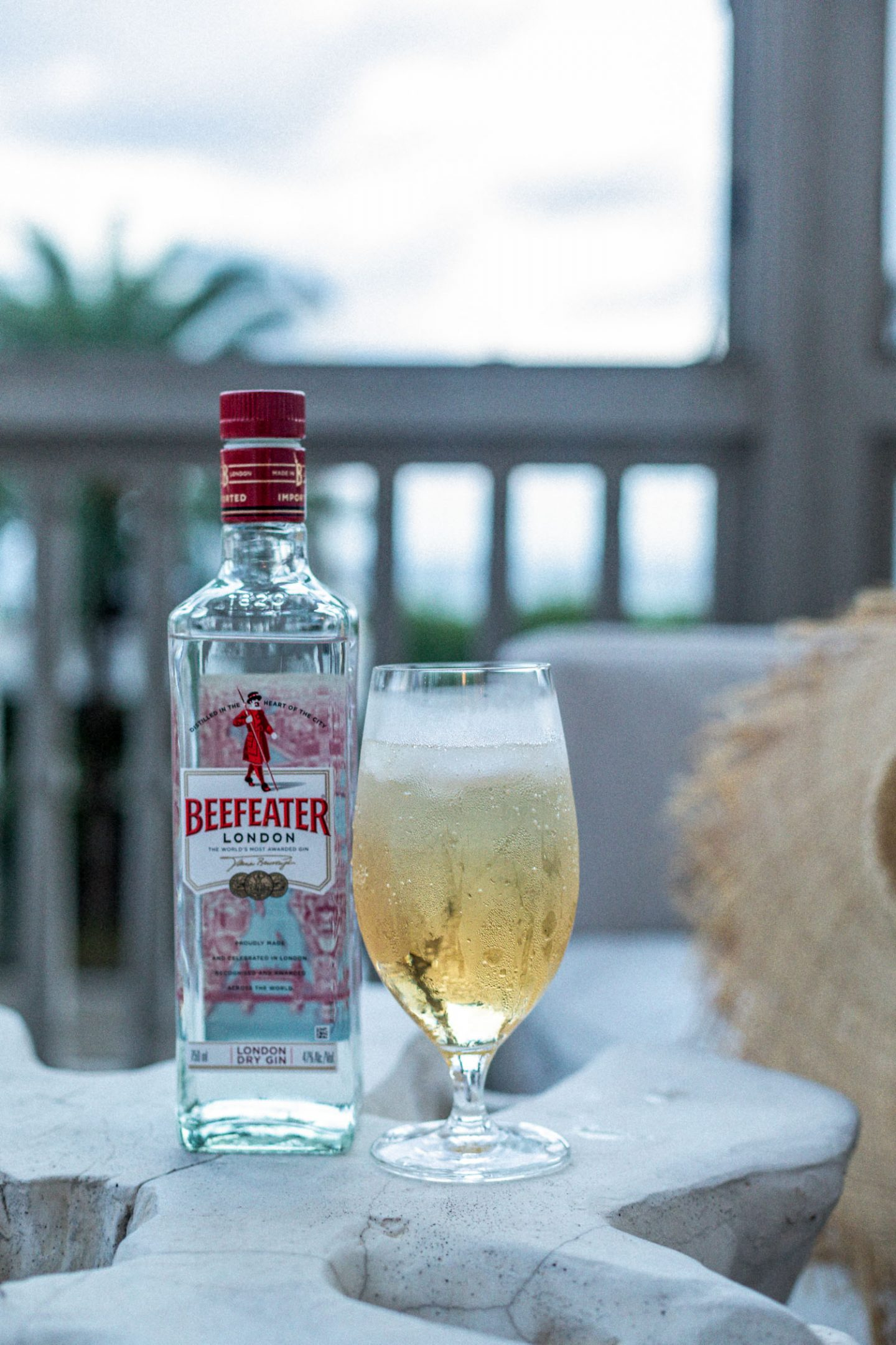 atlanta blogger sitting by the beach drinking cocktail made with beefeater gin, making a cocktail with beefeater gin